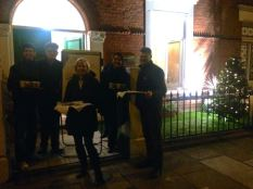 The staff giving mulled wine, hot chocolate & Christmas treats to passers outside the office this week